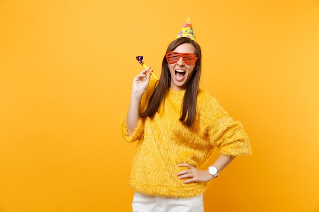 Excited happy young woman in orange funny eyeglasses birthday party hat with playing pipe celebrating isolated on bright yellow background. people sincere emotions lifestyle concept. advertising area.