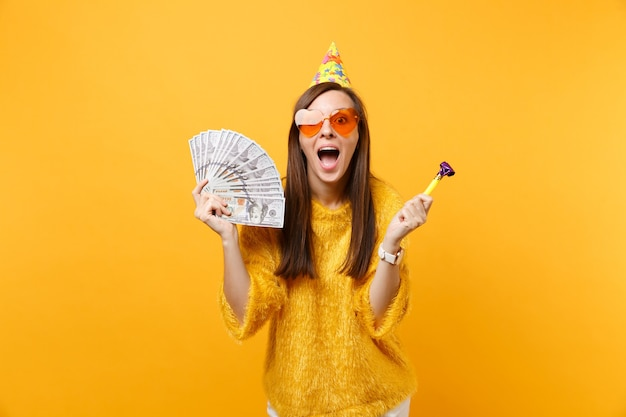 Excited happy young woman in orange heart glasses, birthday hat with playing pipe hold bundle lots of dollars, cash money celebrating isolated on yellow background. people sincere emotions, lifestyle.