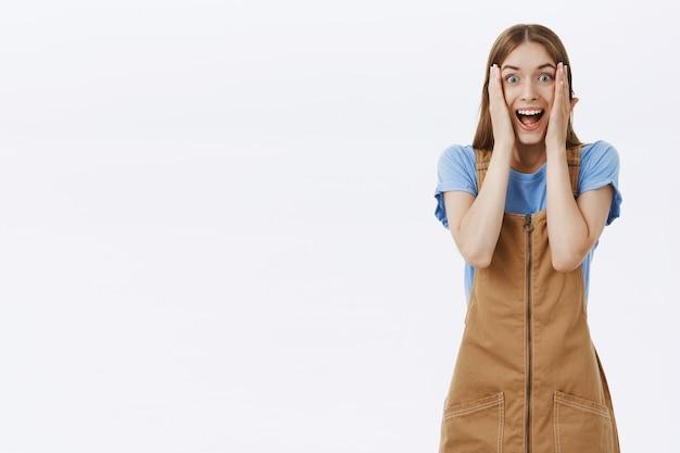 La giovane donna eccitata e felice reagisce alle notizie impressionanti