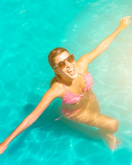 Excited happy young woman standing in pool