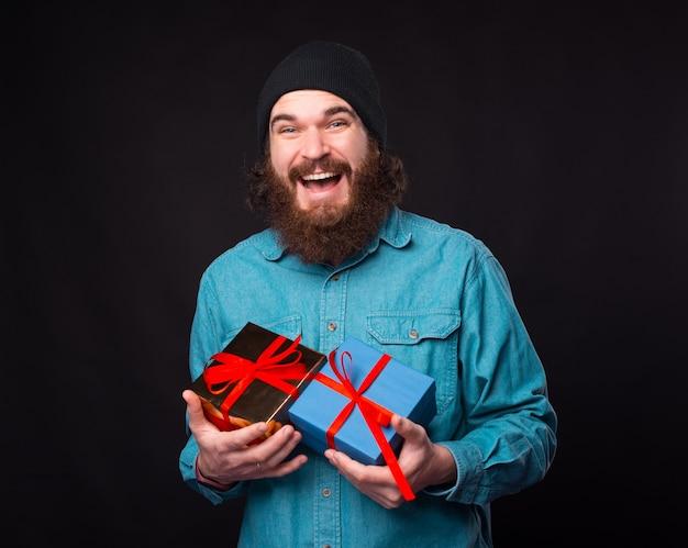 흥분된 힙 스터 블루 셔츠는 선물 상자를 들고있다.