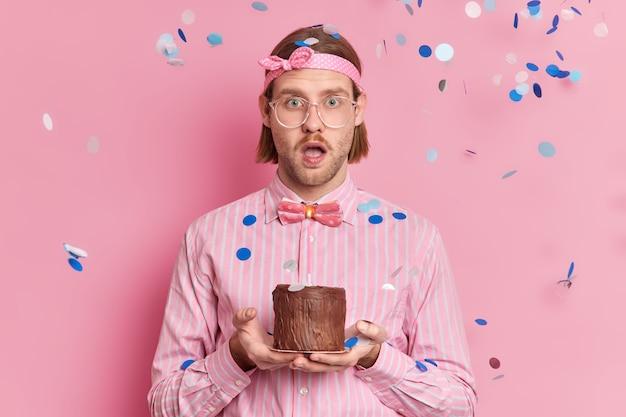 ボブの髪型を持つ興奮した流行に敏感な男は、お祝いの衣装を着て、飛んでいる紙吹雪でピンクの壁に対して驚きのポーズを受け取るためにショックを受けたチョコレートケーキを保持します