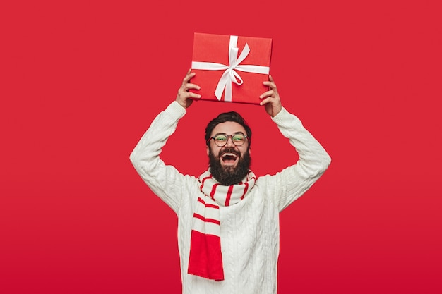 Excited hipster shaking christmas present over head