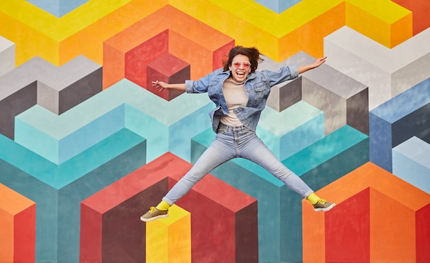 Возбужденная хипстерская женщина прыгает высоко на красочном фоне