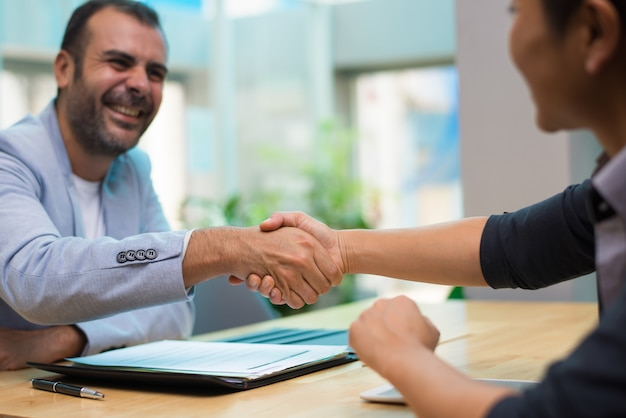 Excited hispanic employer congratulating new employee