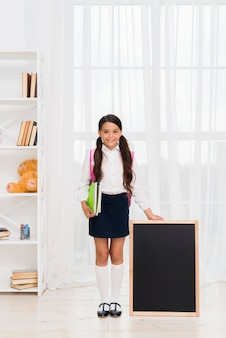 Excited hispanic schoolgirl with copybooks and chalkboard