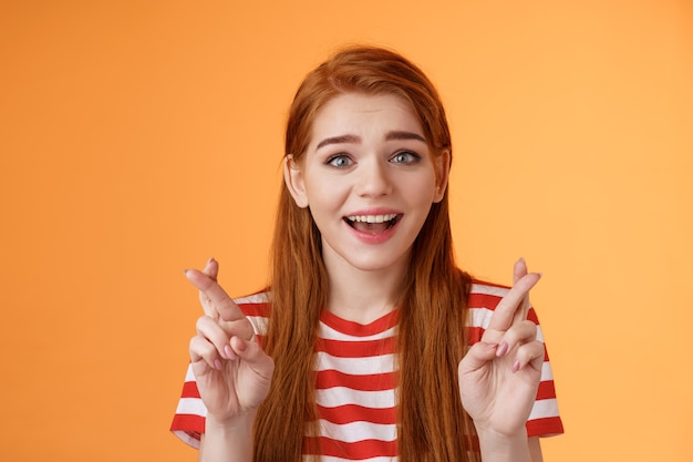 興奮した希望に満ちた赤毛の女の子の希望は宝くじに当選し、楽観的に笑い、信仰を見て、夢が叶うと信じ、幸運を交差させ、願い事をし、良いニュースを期待し、幸運を祈り、オレンジ色の背景