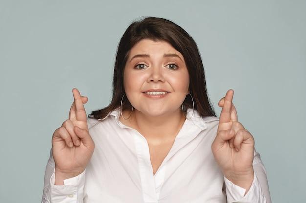 Eccitato promettente giovane plus size dipendente femminile in camicia formale incrociando le dita per buona fortuna prima del colloquio di lavoro. ragazza studentessa bruna in sovrappeso che spera per il meglio, in posa con le dita incrociate