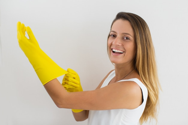 Excited housewife putting rubber glove on hand