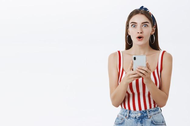 Donna elegante attraente eccitata e impressionata in top a strisce che tiene smartphone piegando le labbra con stupore guardando il gesto stupito e incuriosito
