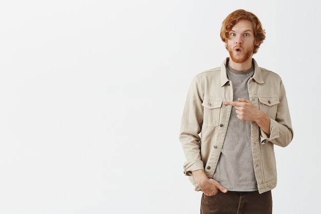 Excited and impressed bearded redhead guy posing against the white wall