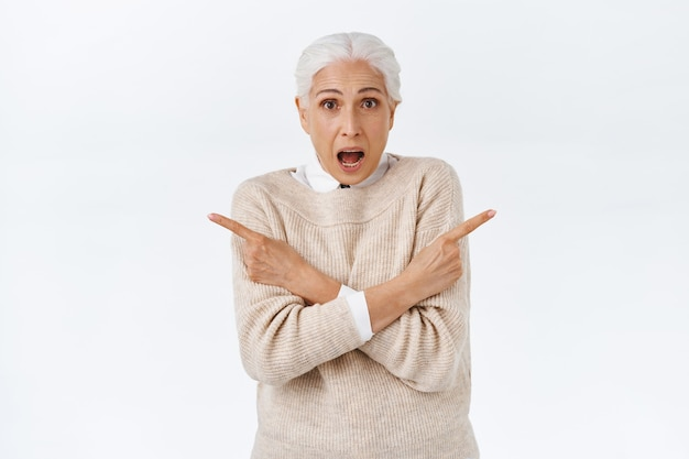 Excited and indecisive senior lady with grey combed hair, wear elegant sweater over blouse, cross arms over chest, pointing left and right sideways and talking to camera astonished, asking question