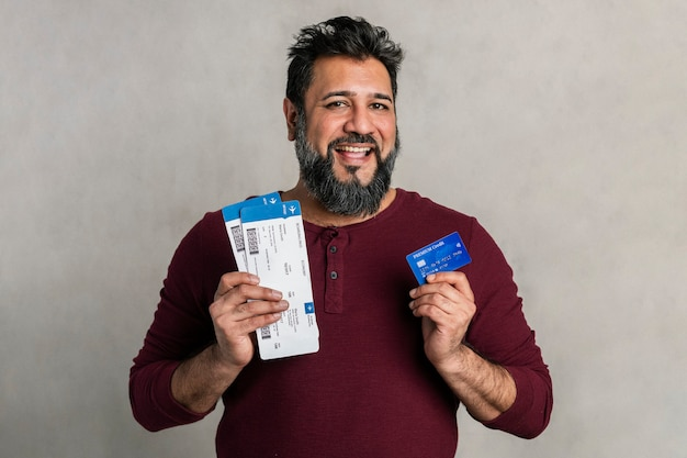 Excited indian man holding a credit card and flight tickets