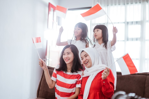 Excited indonesian family supporter while watching sport match at television at home together