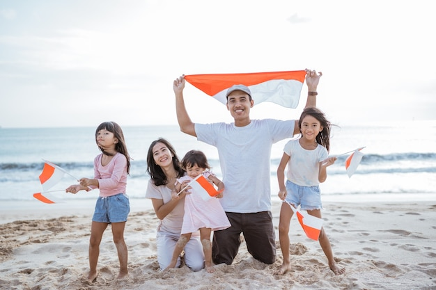 Excited indonesian family supporter with indonesian flag in the beach together