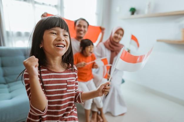 Взволнованный сторонник маленькой девочки из индонезии во время просмотра спортивного матча по телевизору дома с семьей на заднем плане