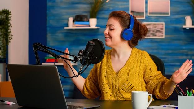 거실 스튜디오에서 동영상 블로그를 녹음하는 흥분된 인플 루 언서가 마이크에서 말하는 팟 캐스트 콘텐츠 제작