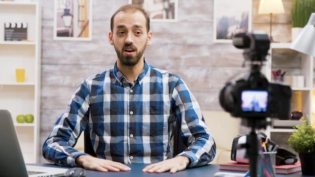 Influencer entusiasta mentre registra per il suo vlog in salotto. famoso uomo creativo.
