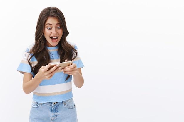 Eccitata, intensa, moderna, geek, bella donna, tenere il cellulare in orizzontale, gridare allo schermo dello smartphone, guardare il display mentre gioca a un gioco duro, superare il livello difficile
