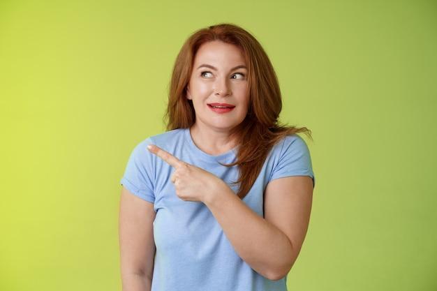 흥분된 흥미 진진한 중년 성숙한 빨간 머리 여자를 쳐다보고 왼쪽 복사 공간을 가리키는 호기심 스릴 미소