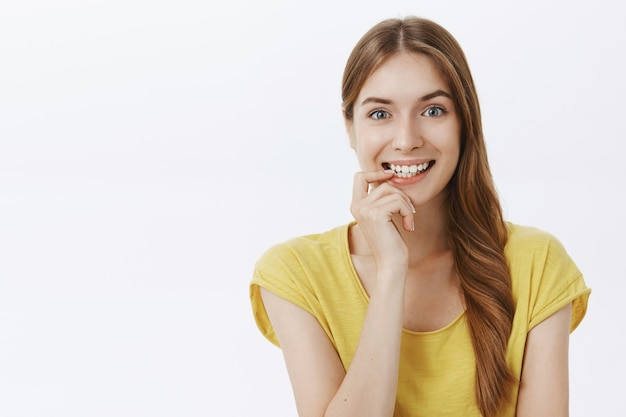 Ragazza sorridente eccitata e incuriosita, tentata di provare qualcosa di interessante, sembrando premurosa