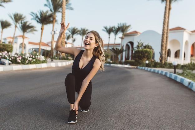 Возбужденная радостная удивительная счастливая женщина работает в парке солнечным утром. улыбка с закрытыми глазами, выражение позитива, истинные эмоции, здоровый образ жизни, тренировки.
