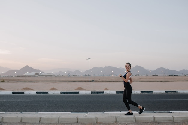Возбужденная радостная удивительная счастливая женщина, бегущая по дороге тропической страны. улыбаться, выражать позитив, настоящие эмоции, здоровый образ жизни, тренировки ..