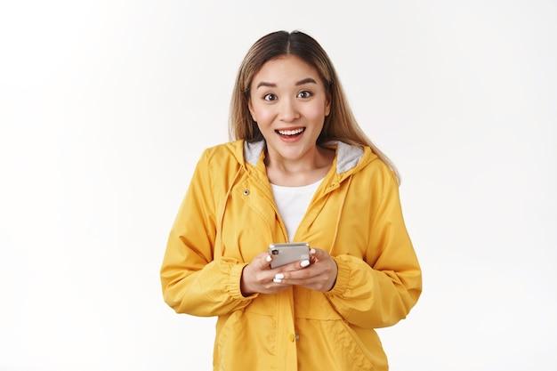 Eccitato gioioso carismatico giovane moderno asiatico ragazza bionda fasciata fantastico nuovo gioco per smartphone non può smettere di giocare app guarda macchina fotografica divertito stupito sorriso tenere cellulare