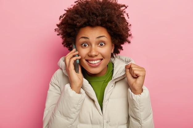 흥분된 즐거운 어두운 피부의 여성이 주먹을 쥐고, 스마트 폰으로 채팅하고, 회의 세부 사항을 논의하고, 전화 통화를하고, 따뜻한 겨울 겉옷을 입고 기꺼이 카메라를 바라 봅니다.