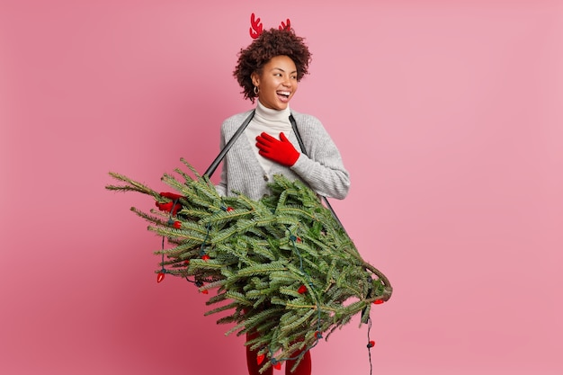 興奮したうれしそうな女性ギタリストが、大晦日にギターを弾くふりをしてモミの木を抱き、赤い手袋をはめてトナカイの角が目をそらし、お祝いのイベントの準備をします。クリスマスの頃