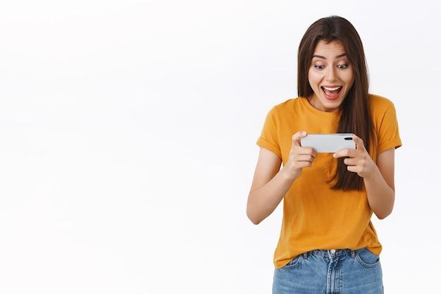 노란색 티셔츠를 입은 신나고 즐거운 미모의 여성이 스마트폰을 수평으로 들고 환호하고 웃고 휴대폰 디스플레이를 보고 놀라고 재미있는 새로운 모바일 게임을 하고 있습니다