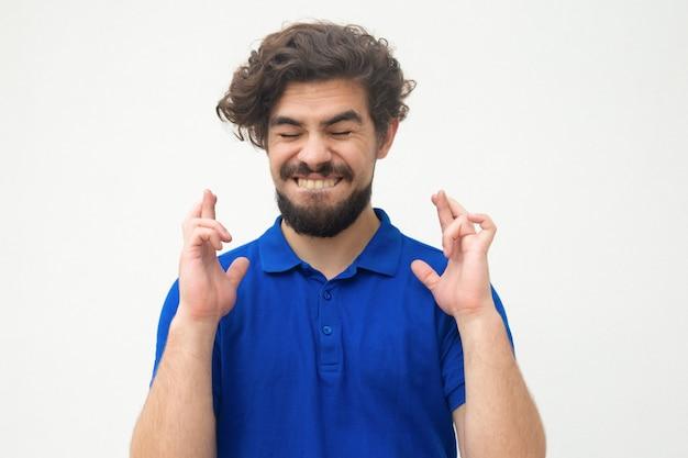 Excited joyful guy keeping fingers crossed