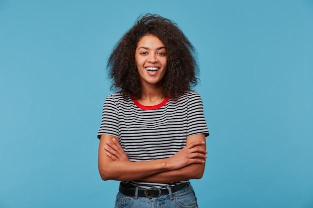 Eccitato gioiosa giovane donna felice con acconciatura afro ridendo sorridente in piedi con le braccia incrociate