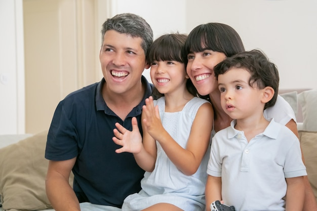 Excited joyful parent couple with two kids watching tv, sitting on couch in living room, looking away and smiling.