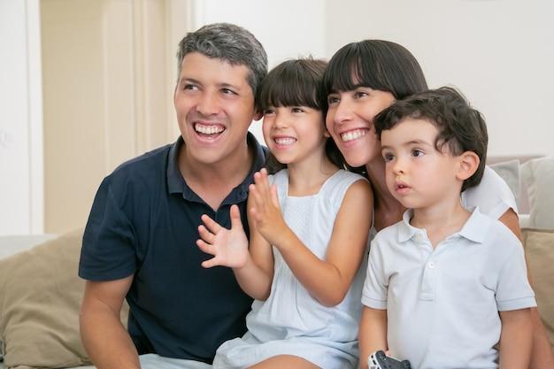 Взволнованная радостная родительская пара с двумя детьми смотрит телевизор, сидя на диване в гостиной, глядя в сторону и улыбаясь.
