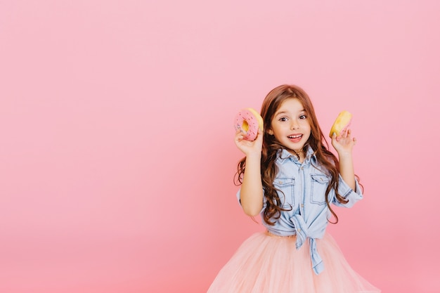 Excited joyful young pretty girl in tulle skirt expressing positivity, having fun to camera with donuts isolated on pink background. happy childhood with tasty dessert. place fot text