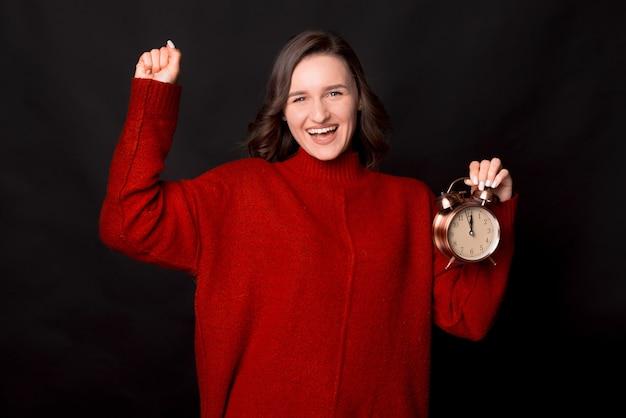 빨간 스웨터에 흥분된 즐거운 젊은 여성이 승자 제스처를 하 고 시계를 개최