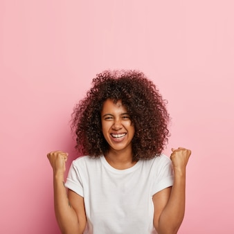 Excited joyous young cute woman raises clenched fists, stands without make up against pink wall, has curly bushy hair, celebrates victory and triumph, wears white everyday t shirt. oh yes!