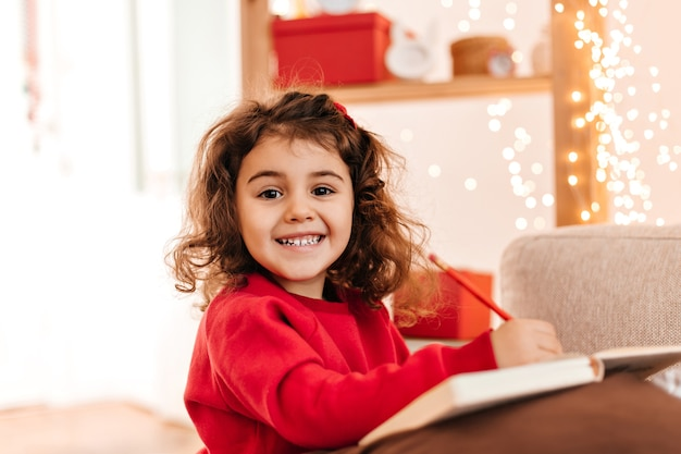 Excited kid drawing with smile. indoor shot of brunette child with pen and notebook.