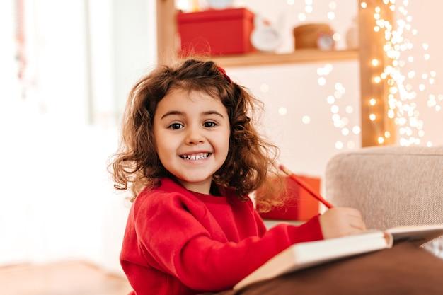 笑顔で描く興奮した子供。ペンとノートブックでブルネットの子供の屋内ショット。