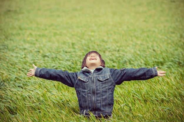 美しい緑の黄色の芝生のフィールドで興奮した子供