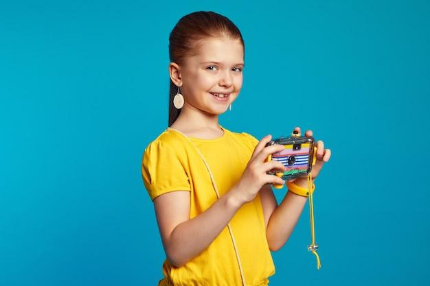 Взволнованный ребенок-фотограф держит камеру, стоя изолированно над синим