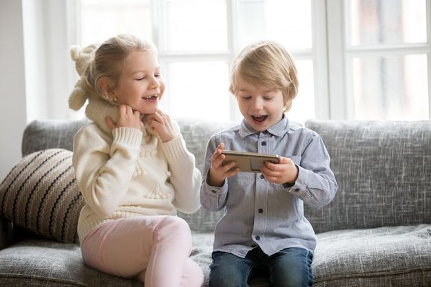 Excited kids having fun using smartphone sitting together on sofa
