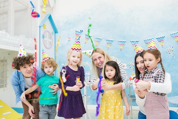 Возбужденные дети смотрят на падающее конфетти от крекеров