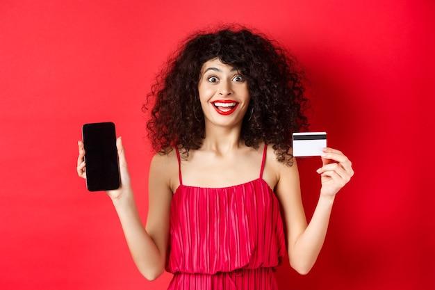 プラスチック製のクレジットカードとスマートフォンの画面を表示し、驚いて笑って、スタジオの背景に立っている赤いドレスの興奮した女性。