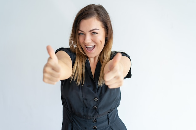 Excited lady showing thumbs up and looking at camera
