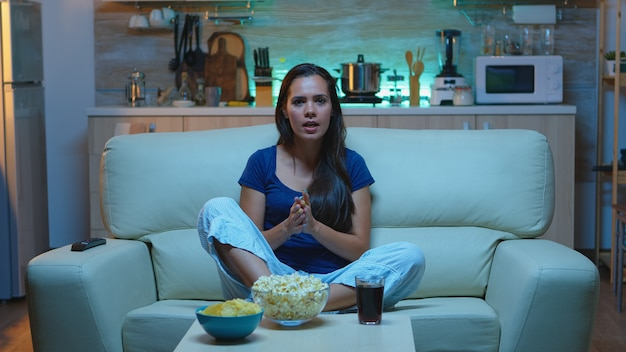 Excited lady supporting favorite player watching tv at home in the evening. sports fan in pajamas screaming on tv at fotball competition sitting on couch in living in front of television.