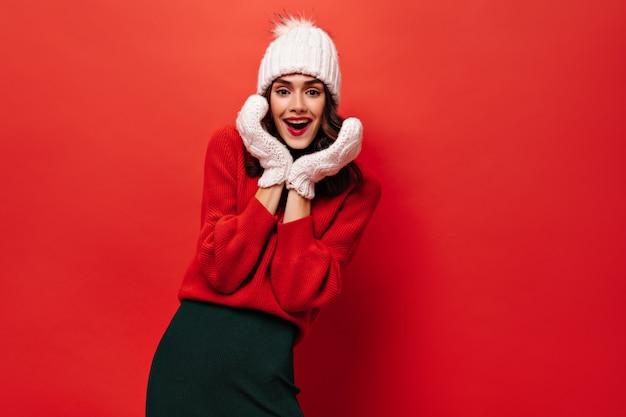 Возбужденная дама с яркими губами в вязаной шапке и варежках улыбается на красной стене