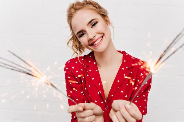 白い壁に線香花火を保持している流行のメイクで興奮した女性。ベンガルライトでポーズをとるブロンドの髪のかなり幸せな女の子。