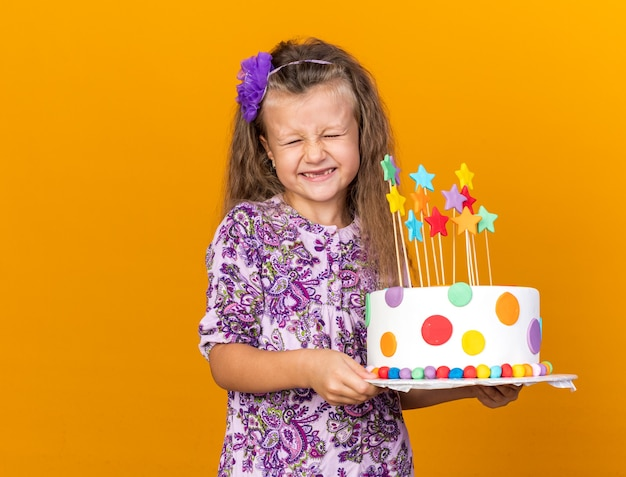 Excited little blonde girl holding birthday cake isolated on orange wall with copy space